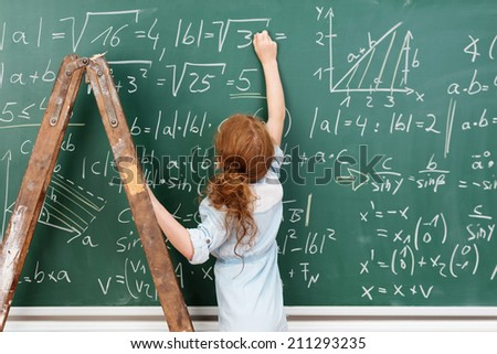 Little girl genius working on a mathematical equation standing on a wooden stepladder to reach the blackboard as she completes the answers