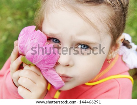 Little girl gently presses to cheek a big pink flower - stock photo