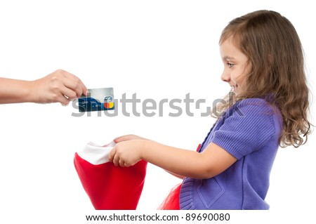 little girl gets credit card from her mother as a present for christmas. Daughter holding santa hat and mother putting card in it. Studio shot, isolated on white background. - stock photo