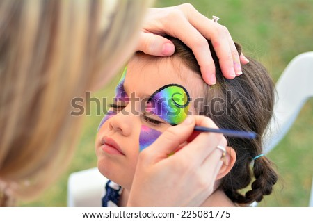 little girl getting her face painted like a butterfly by face painting artist.  - stock photo