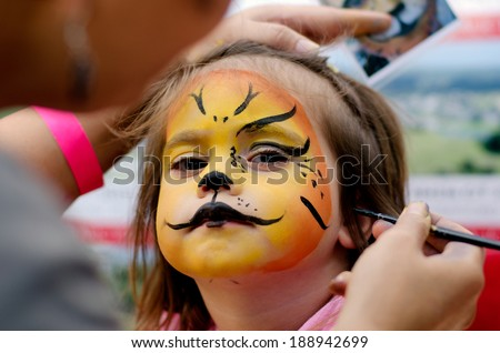 little girl getting her face painted like a lion by face painting artist. - stock photo