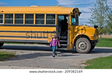 little girl getting off a school bus - stock photo