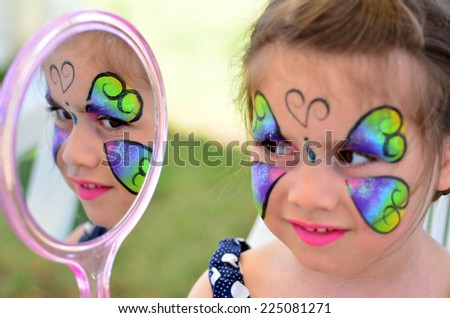 little girl getting with face painting looks at the mirror. Focus on mirror reflection - stock photo