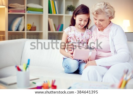 Little girl giving a gift box to her grandmother - stock photo