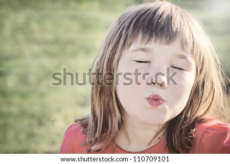 Little girl giving an air kiss in evening sunlight, with vintage editing