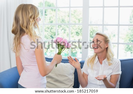 Little girl giving flower bouquet to surprised mother in living room - stock photo