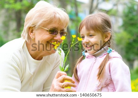 little girl giving her great grandmother yellow flowers - stock photo