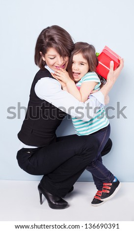little girl giving her mom a present on blue background - stock photo