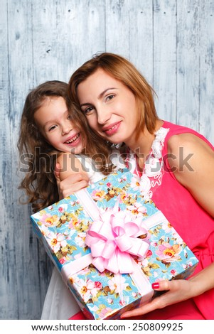 little girl giving her mom a present , the day of mothers - stock photo