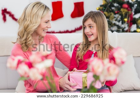 Little girl giving her mother a christmas gift at home in the living room - stock photo