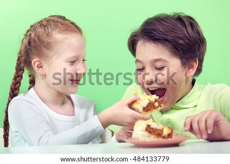 Little girl giving piece of pie to her boyfriend