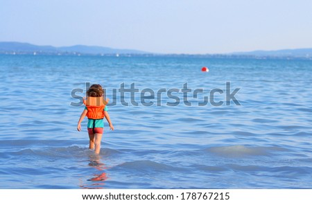 Little girl goes into the water for her ball - stock photo