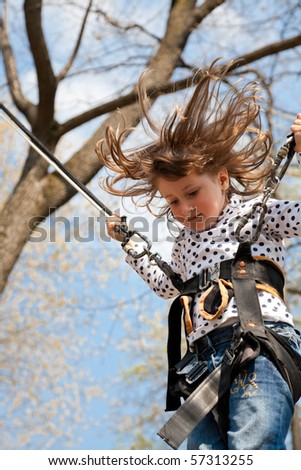 Little girl going up and down on a bungee. - stock photo