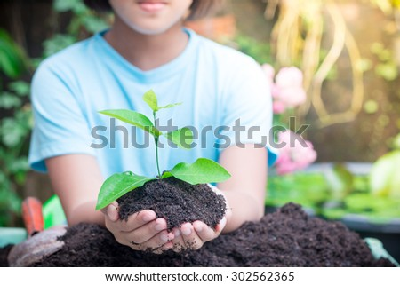 Little girl hands holding little sprout with care in nature green background - stock photo