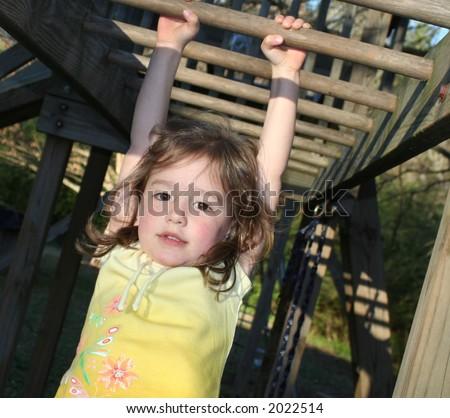 little girl hanging from monkey bars - stock photo