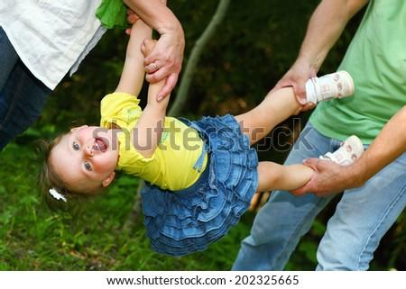 little girl hanging in parents hands - stock photo