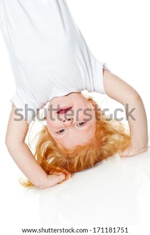 Little girl hanging upside down - stock photo