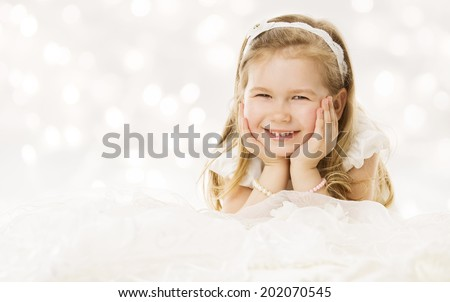 Little girl happy smiling, lying down hands under cheeks. White background - stock photo