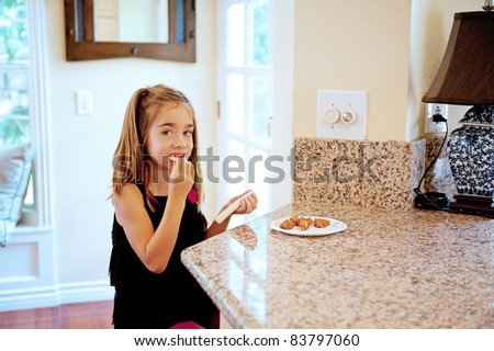 Little girl has a snack of cookies and string cheese in the kitchen after school - stock photo