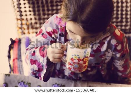 little girl has breakfast with green tea - stock photo