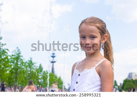 Little girl have fun in outdoor fountain at hot day - stock photo