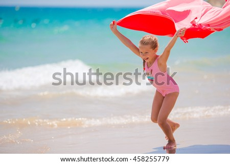 Little girl have fun with beach towel during tropical vacation - stock photo