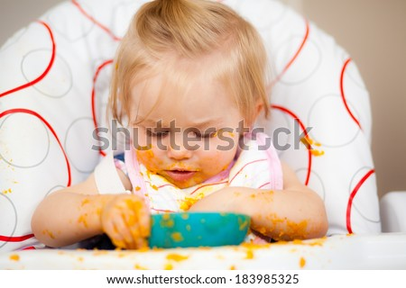 Little girl having a messy lunch - stock photo