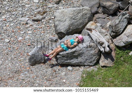 little girl having a sunbath on a big stone at the Lago Maggiore in Italy