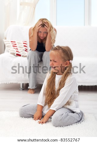 Little girl having a temper tantrum with her desperate mother in background - stock photo