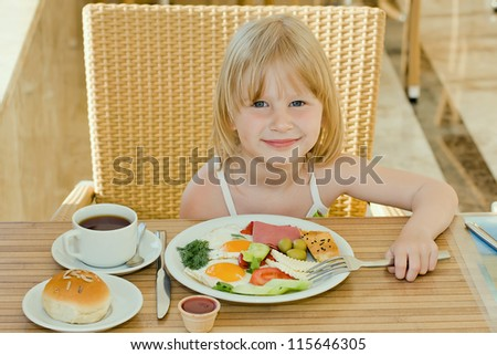 Little girl having breakfast - stock photo