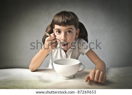 Little girl having breakfast - stock photo