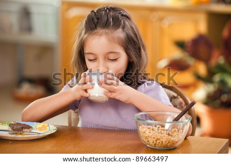 little girl having breakfast: drinking a glass of milk
