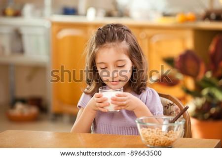 little girl having breakfast: drinking a glass of milk - stock photo