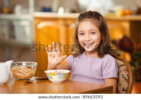 little girl having breakfast: laughing at sticky cereals on her hand - stock photo
