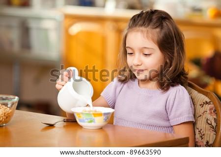 little girl having breakfast:pouring milk in the bowl - stock photo