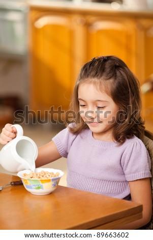 little girl having breakfast: pouring milk in the bowl - stock photo
