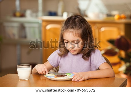 little girl having breakfast: spreading chocolate cream on a slice of bread