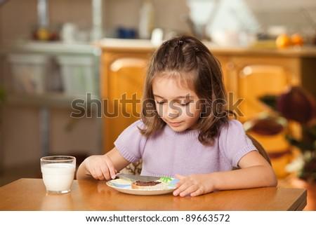 little girl having breakfast: spreading chocolate cream on a slice of bread - stock photo