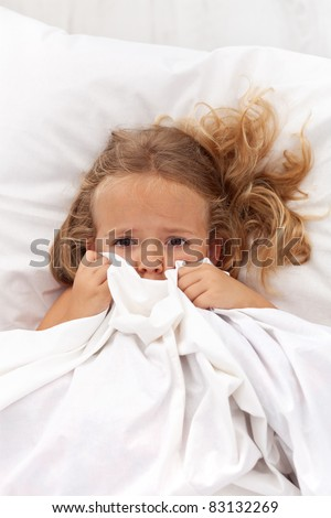 Little girl having childhood nightmares and fears hiding under the quilt - stock photo