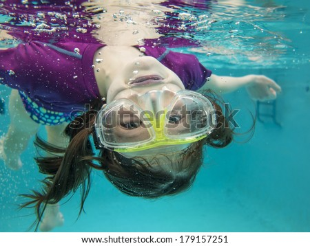 little girl having fun and swimming upside down underwater - stock photo