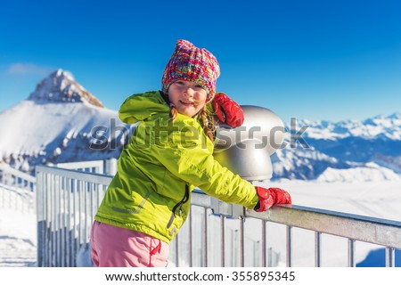 Little girl having fun during winter vacation in mountains, swiss Alps - stock photo