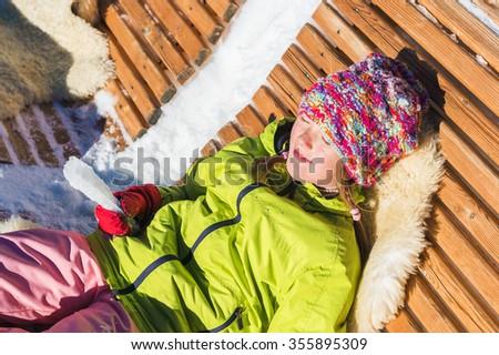 Little girl having fun during winter vacation in mountains, swiss Alps, taking sun bath  - stock photo