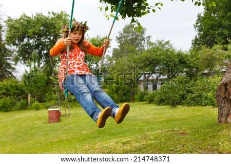 Little girl having fun in garden swings - stock photo