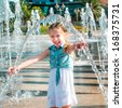 little  girl having fun in splashes a fountain - stock photo