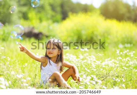 Little girl having fun in summer day, soap bubbles - stock photo