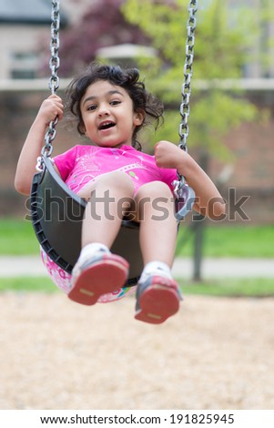 Little Girl Having Fun on a Swing in a Park - stock photo
