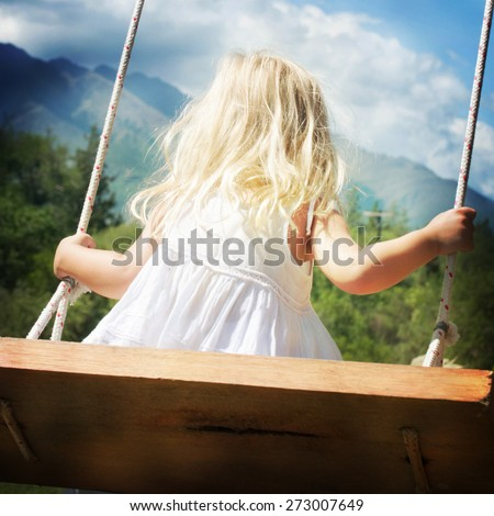 Little girl having fun on a swing outdoor - stock photo