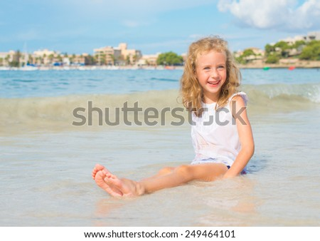 Little girl having fun on beach vacation. Place for text. - stock photo