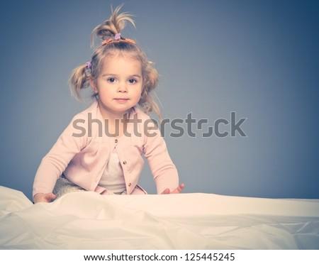 Little girl having fun on bed - stock photo