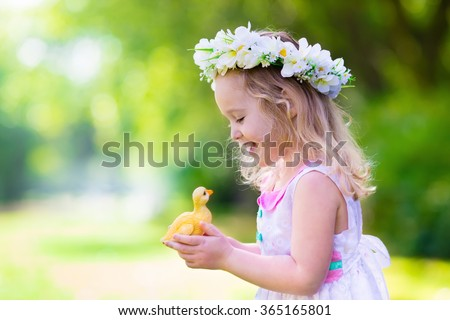 Little girl having fun on Easter egg hunt. Kid in flower crown playing with toy duck or chicken. Children searching for eggs in the garden. Toddler kids outdoor. Happy child laughing and smiling. - stock photo